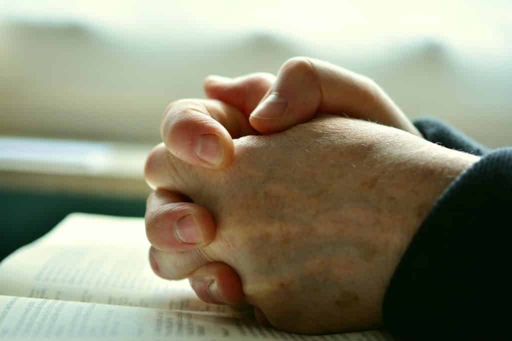 Hand Praying on Top of Bible